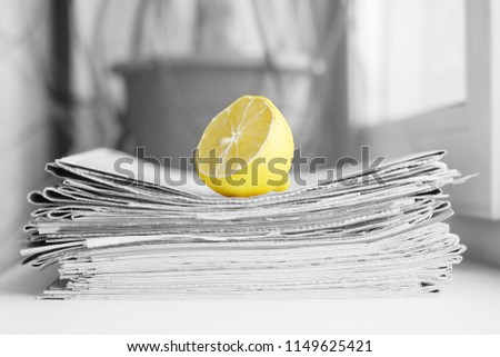 Stack of newspapers and lemon. Daily journals with headlines and articles and fresh fruits. Concept for juicy news                                #1149625421