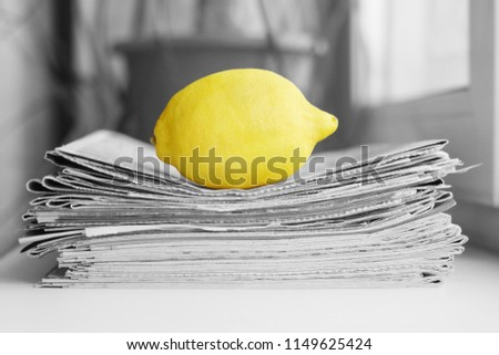 Stack of newspapers and lemon. Daily journals with headlines and articles and fresh fruits. Concept for juicy news                                #1149625424