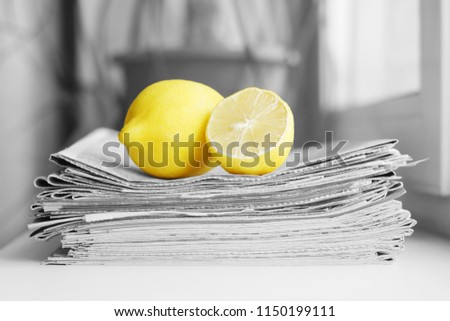 Stack of newspapers and lemon. Daily journals with headlines and articles and fresh fruits. Concept for juicy news                                 #1150199111