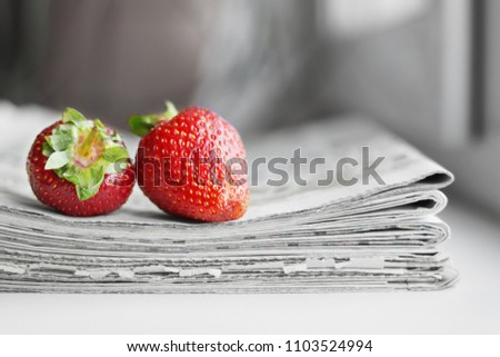 Stack of newspapers and strawberries. Daily journals with headlines and articles and fresh fruits. Concept for juicy news                             #1103524994