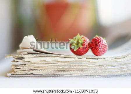 Stack of newspapers and strawberries. Daily journals with headlines and articles and fresh fruits. Concept for juicy news                                      #1160091853