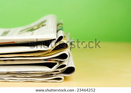 Stack of newspapers lying on the table on green background