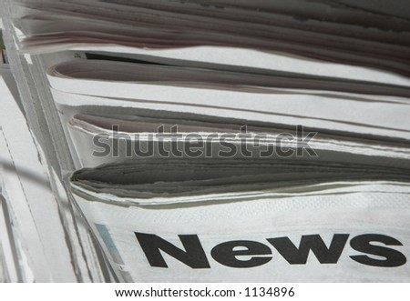 Stack of newspapers with focus on the word 'news' on top paper.