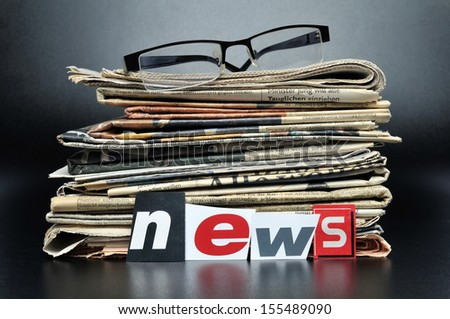 Stack of newspapers with glasses on top