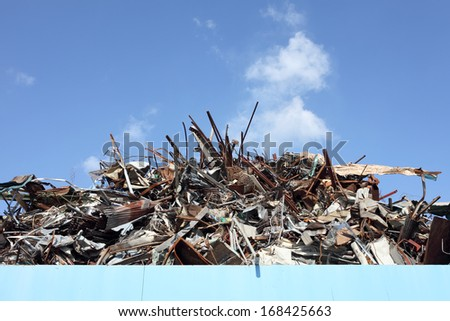 Stack of old and rusty metal against the blue sky