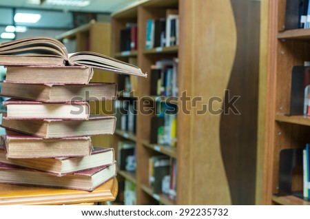 stack of old book on the desk in library blur background