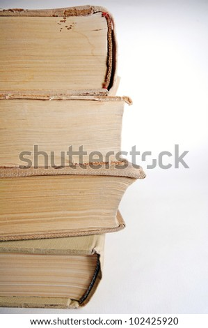 Stack of old books on light grey background. Copy space on right.