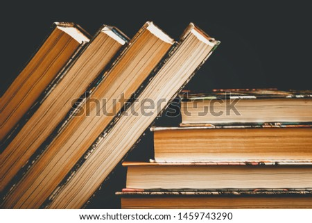 Stack of old books, textbooks on a black background, classic literature