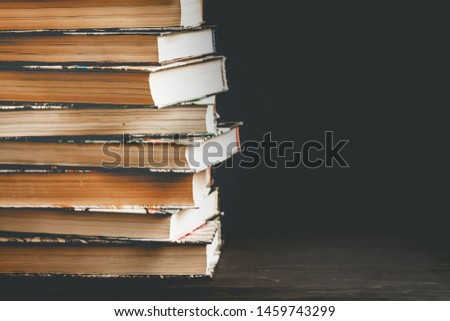 Stack of old books, textbooks on a black background with copy space