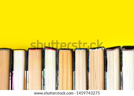 Stack of old books, textbooks on a yellow background, literature concept