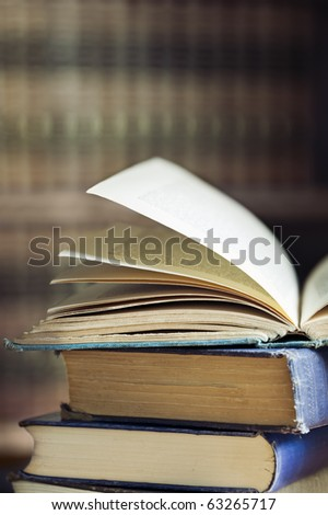 Stack of old books, with defocused bookshelves behind. - stock photo