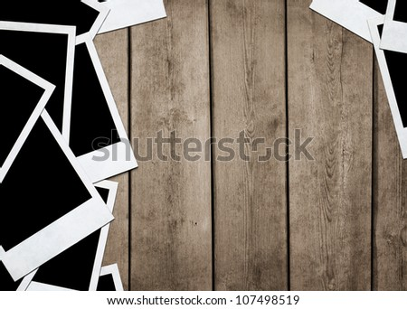 Stack of old instant photos at grunge wooden background