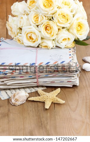 Stack of old letters and bouquet of pastel yellow roses on wooden table. Romantic vintage setting. Copy space