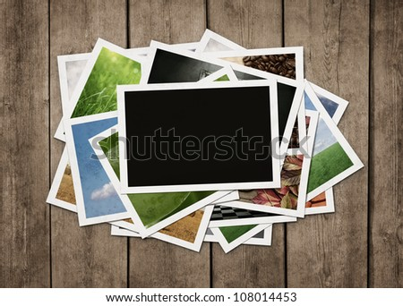 Stack of old photographs at grunge wooden background with clipping path for the blank one