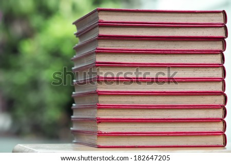 stack of old red cover book on wooden  table