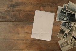 stack of old vintage monochrome photographs 1950 on photographic paper on natural wood background, concept of genealogy, memory of ancestors, family tree, nostalgia, childhood, remembering