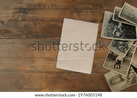 stack of old vintage monochrome photographs 1950 on photographic paper on natural wood background, concept of genealogy, memory of ancestors, family tree, nostalgia, childhood, remembering Foto stock ©