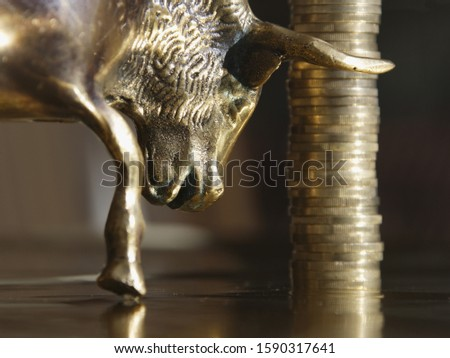 Stack of One Euro coins next to bull figurine