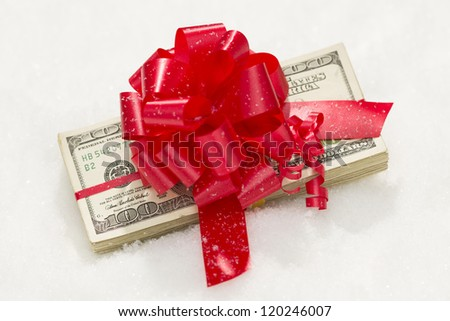 Stack of One Hundred Dollar Bills with Red Ribbon on Snow Flakes.