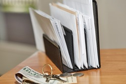 Stack of open and unopened envelopes in a desk organizer with keys, coins and dollar bills and shallow depth of field