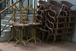 Stack of outdoor tables and chairs of cafe linked by metal chain, which closed during pandemic of COVID-19 virus. COVID-19 restrictions on public cafe.