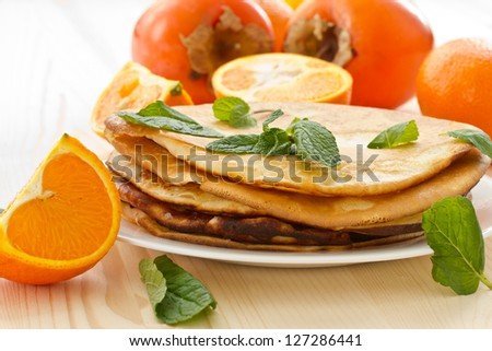 stack of pancakes on a plate of various fruits - stock photo