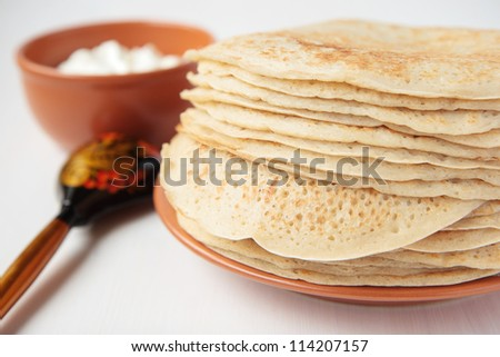 Stack of pancakes on ceramic plate, sour cream, painted wooden spoon