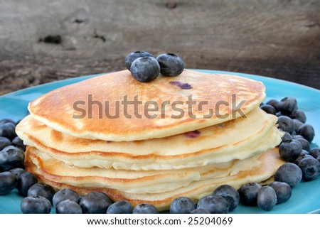 Stack of pancakes with fresh blueberries all on a blue plate.