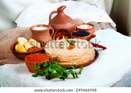 stack of pancakes with red and black caviar in a still life with pottery and jug with milk