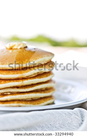 Stack of pancakes with syrup served outdoors.