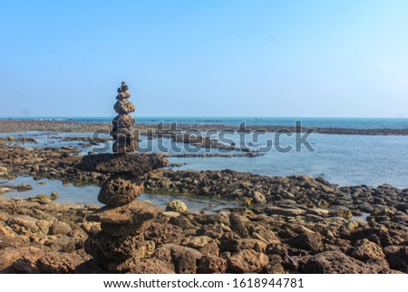 Stack of pebbles balancing one on another, making a tower. Close-up shot on pebble beach with the sea/ocean in the background; sunny day.