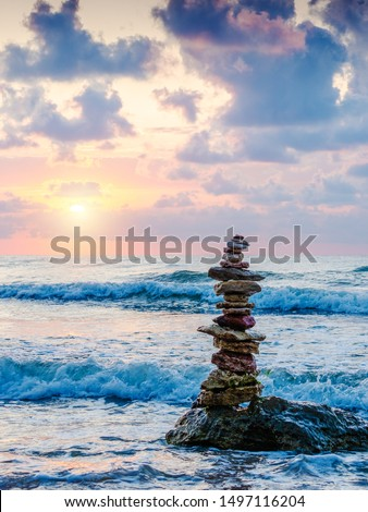 Stack of pebbles on beach with sun and beautiful sky on background