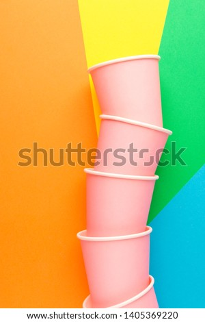 Stack of pink paper drinking cups on multicolored pinwheel background. Funky retro style. Birthday party fest celebration kids fun. Nature friendly recyclable materials concept. Cope space #1405369220