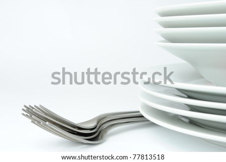 stack of plates and forks on a white background