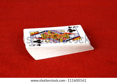Stack of playing cards on red background