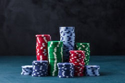 stack of poker chips on a blue table on a black background