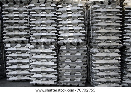 Stack of raw aluminum ingots in aluminum profiles factory - stock photo