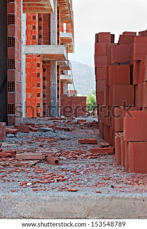 Stack of red building blocks on an untidy construction site