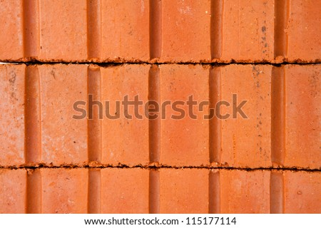 Stack of red clay bricks buldiing a wall