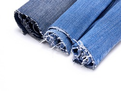 Stack of rolled denim jeans with tattered threads, isolated on white background, with space to text