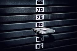 Stack of rusty metal weights in gym bodybuilding equipment