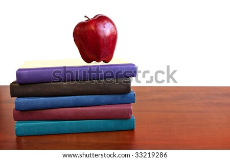 stack of school books with apple on top
