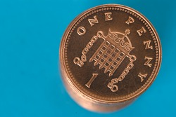 Stack of shiny new one penny coins, against a blue background