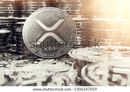 Stack of silver Ripple XRP coins in blurry closeup with lens flare as a symbol of prosperity. 3D rendering