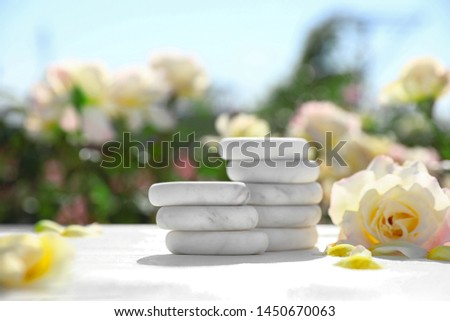 Stack of spa stones and beautiful rose on white table in blooming garden, space for text. Harmony and zen
