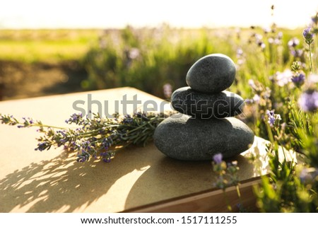 Stack of spa stones on wooden table in lavender field. Harmony and zen