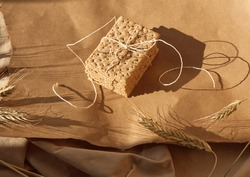 Stack of spelt sesame cracker with ribbon on craft paper background with ears. Minimal food concept. Crispy bread, ray or spelt wheat, sesame seeds. Earth colors, brown tone, monochrome color