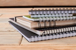 Stack of spiral notebooks on wooden background. Pile of paper notepads with ring binding on wood table. Concept of stationery supplies.