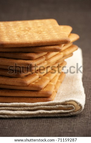 Stack of square crackers close-up on linen napkin. - stock photo