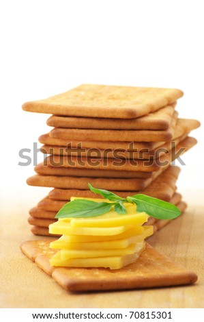 Stack of square crackers with slices of cheese and basil on wooden board against white background.